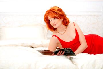 девушка читает журнал лежа на шикарной белой  кровати