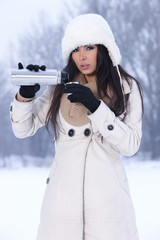 Beautiful woman holding thermos in snowy winter outdoors