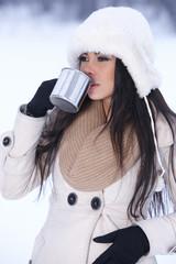 Beautiful holding mug in snowy winter outdoors