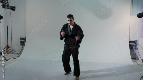 Karate master shows exercise with nunchaku