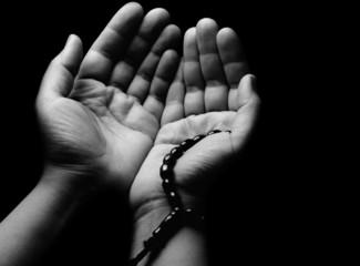 Hands praying in dark