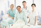 Older patient on bed with hospital crew poster