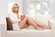 Beauty, blondie woman in a sofa with an orange colored cup