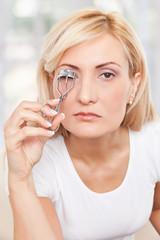 Beauty woman using eyelashes curler