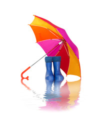 rubber boots and a colorful umbrella with reflection in water