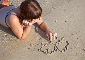 a girl is painting a clover on a sand