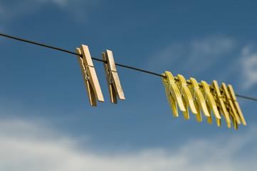 Wäscheklammern vor blauem Himmel
