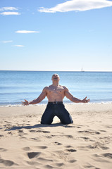 Muscular man kneel on beach and screaming