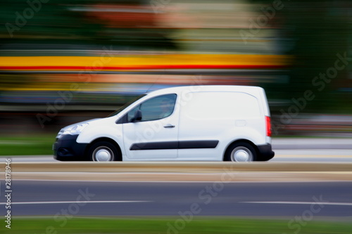 Speedy  white minivan  is  going on road, panning and blur