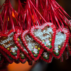 Baked gingerbread hearts hanging on red ribbon outdoors