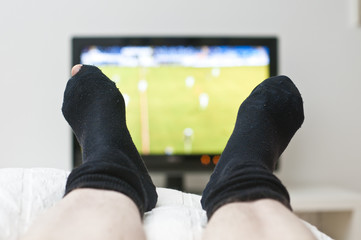 watching a game on tv in dark socks with a hole