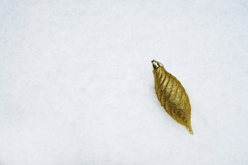Gold bauble on snow