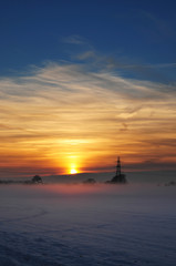 landscape at sunset with fog and snow