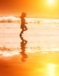 Girl running at sunny sea coastal beach at sunset