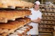 lächelnder bäcker schiebt brotregal - 28216348