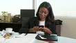 Young businesswoman in office texting on cell phone