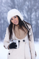 Caucasian woman holding hip-flask on snowy outdoor