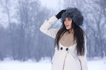 Beautiful brunette in fur cap looking her right