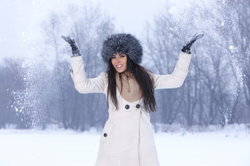 Young woman throwing snow in the air