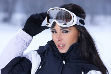 Cute female snowboarder fixing her goggles