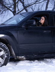Sexy woman in 4x4 car on snowy outdoors