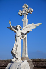 Angel statue and big stone cross on tombs in a cemetery
