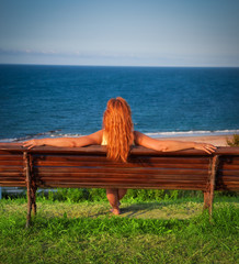 red-haired woman on a bench facing the sea and blue sky