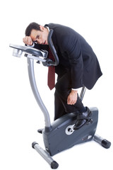 Exhausted Businessman on Exercise Bike Isolated White Background