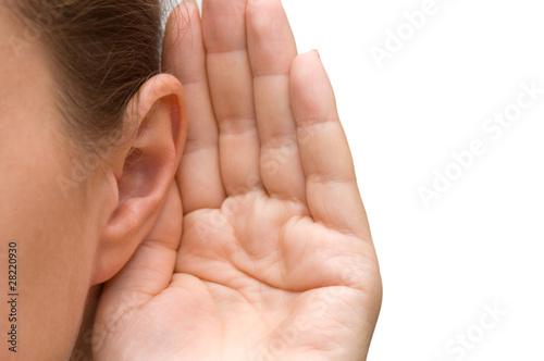 Leinwanddruck Bild Girl listening with her hand on an ear
