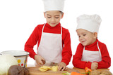 Smiling little chief-cookers on the desk with vegetables poster