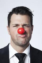 jeune homme d'affaires nez de clown doute