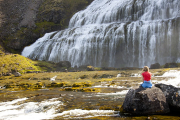 Relax on the rock. In background Dynjandi waterfall - Iceland