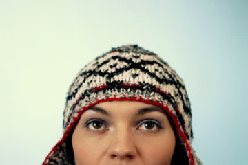 Woman in winter hat looking up over a blue background
