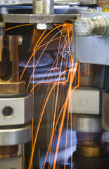 Industrial welding machinery at work, in motion.