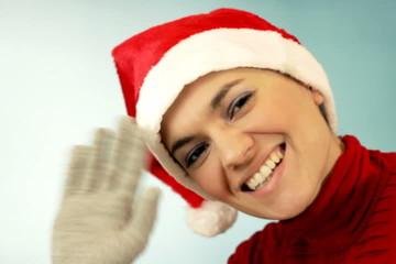 Young smiling woman in santa hat waving hand