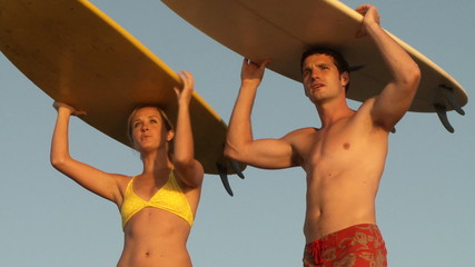 Young couple with surfboards on their heads