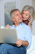 Senior couple at home surfing on internet