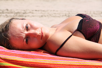 young woman sunbathes lying on chaise lounges