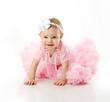 Baby girl wearing pettiskirt tutu and pearls crawling