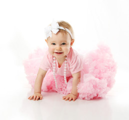 Baby girl wearing pettiskirt tutu and pearls crawling