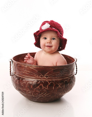 Baby girl sitting in a flower pot
