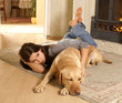 A young woman is laying on the floor with a labrador dog