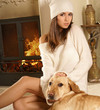 A young woman is sitting on the floor with a labrador dog