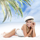 A young and sexy blond in a sailor hat is relaxion on the bed poster