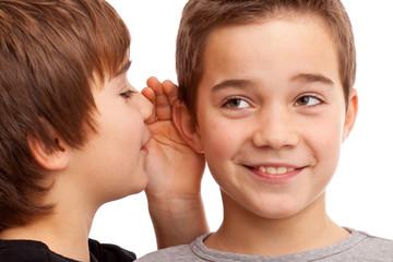 Zwei Jungen flüstern sich News und Geheimnisse ins Ohr