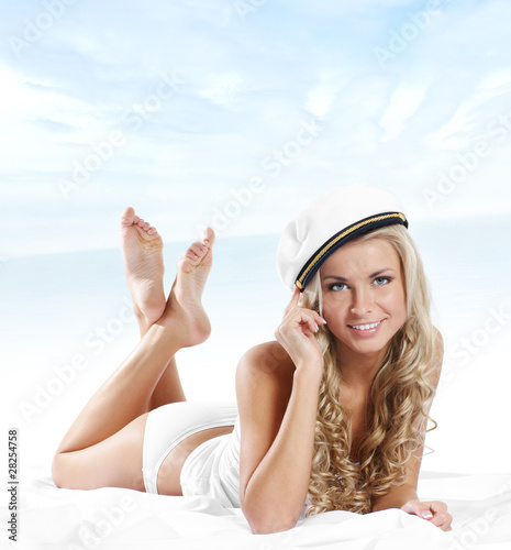 poster of A young and sexy blond in a sailor hat is relaxion on the bed