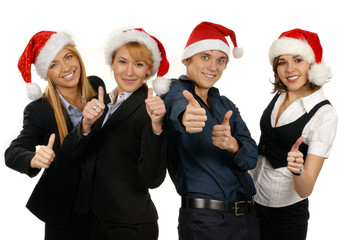 Four young persons are celebrating Christmas in Santa hats