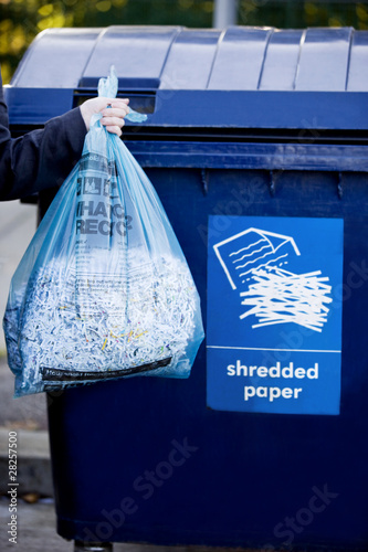 A businessman recycling a bag of shredded paper