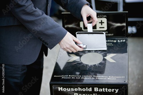 A businessman recycling household batteries
