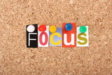 Focus in magazine letters on a cork notice board poster